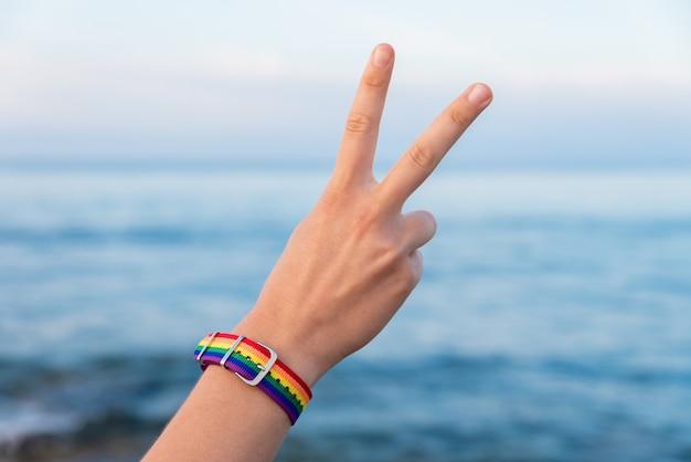 Mão de uma pessoa em uma pulseira colorida gesticulando o sinal v Foto gratuita