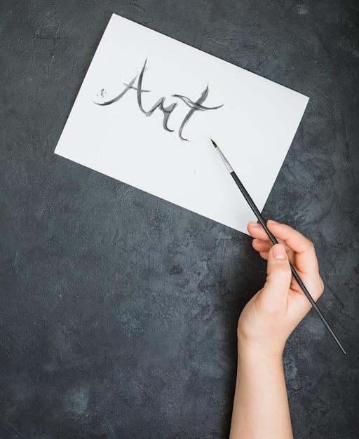 Mão de uma pessoa escrita texto de arte com pincel na folha de papel Foto gratuita