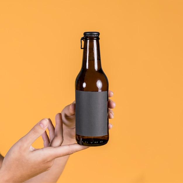 Mão de uma pessoa segurando a garrafa de cerveja sobre fundo amarelo Foto gratuita