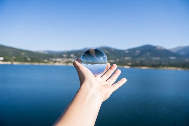 Mão de uma pessoa segurando uma bola de cristal refletindo a paisagem de um lago com montanhas em um reservatório de água em navacerrada Foto Premium