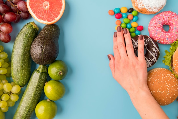 Mão de vista superior, separando alimentos não saudáveis de frutas e legumes Foto Premium