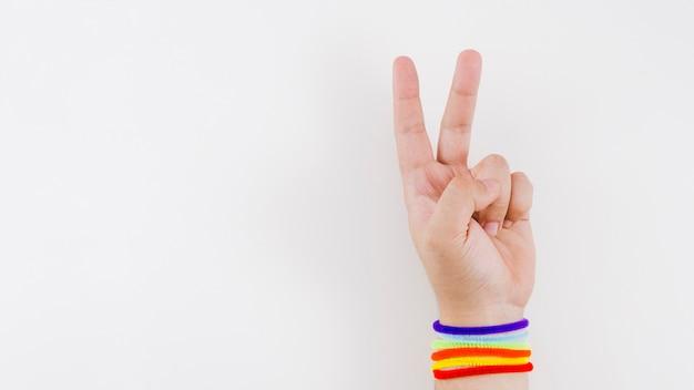 Mão de vitória com pulseira de bandeira do orgulho Foto gratuita
