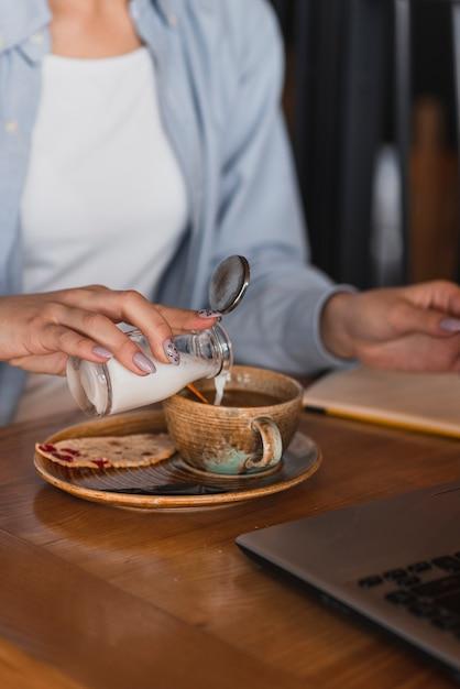 Mão derramando leite em uma xícara de café Foto gratuita