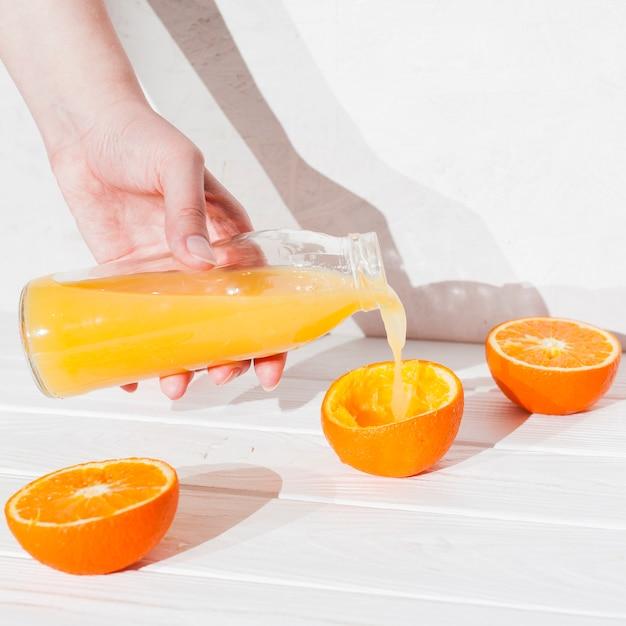 Mão derramando suco em laranja espremida Foto gratuita