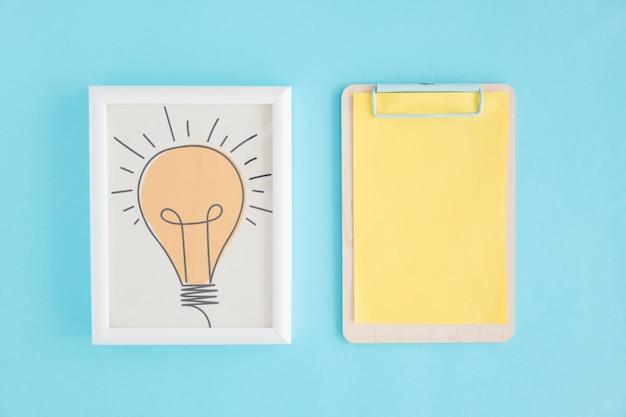 Mão desenhada lâmpada frame e prancheta com papel amarelo Foto gratuita