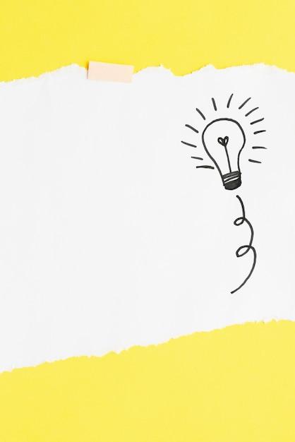 Mão desenhada lâmpada no papel cartão branco sobre o pano de fundo amarelo Foto gratuita