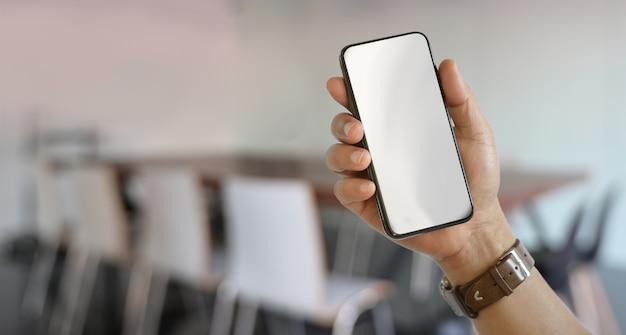 Mão direita do homem segurando o smartphone de tela em branco Foto Premium