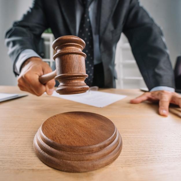 Mão do advogado batendo o martelo de madeira no bloco de som Foto gratuita