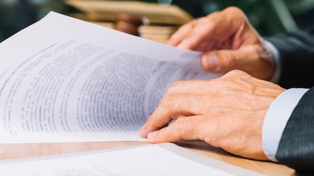 Mão do advogado masculino segurando o documento na mesa no tribunal Foto gratuita