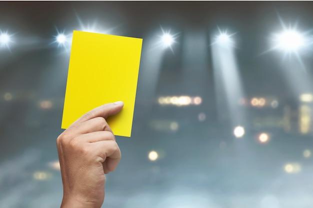 Mão do árbitro com cartão amarelo Foto Premium
