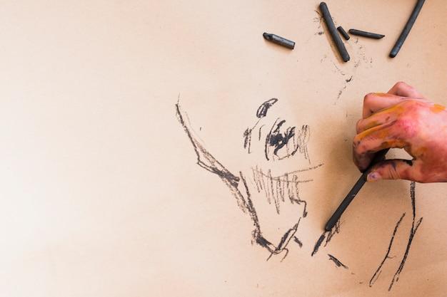 Mão do artista esboçar o desenho com carvão no papel Foto gratuita