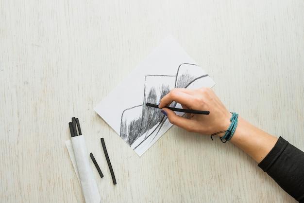 Mão do artista esboçar o desenho em papel branco com pau de carvão Foto gratuita