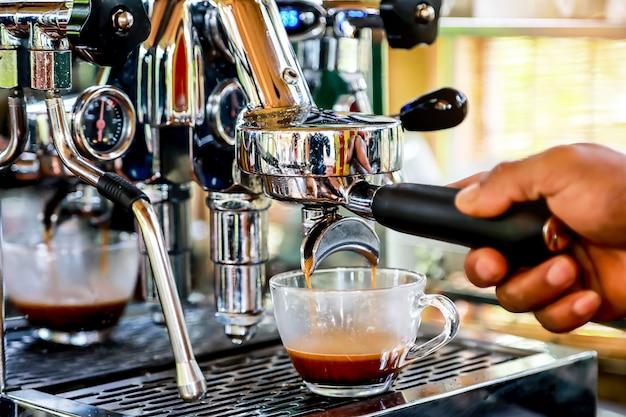 Mão do barista que faz o café do café com a máquina de café na cafetaria. Foto Premium