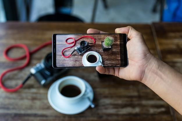 Mão do blogger que guarda o telefone esperto que toma a foto do café e da câmera na tabela. Foto Premium