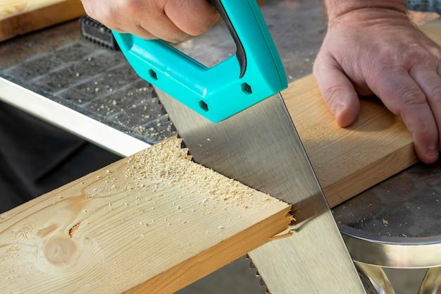 Mão do carpinteiro com as placas de madeira do corte do handsaw. Foto Premium