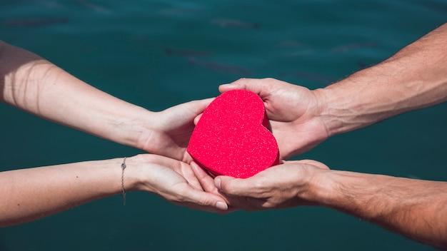 Mão do casal segurando coração vermelho contra o fundo da água do mar Foto gratuita