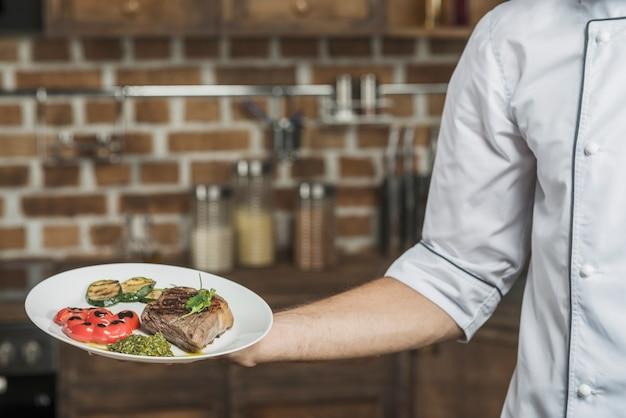 Mão do chef masculino segurando delicioso prato de bife com legumes assados Foto gratuita
