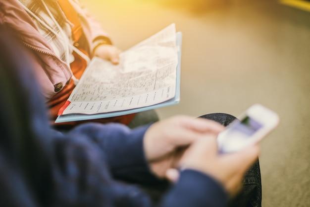 Mão do close up do turista dois com mapa e que procura o lugar na profundidade de campo rasa do smartphone. Foto Premium