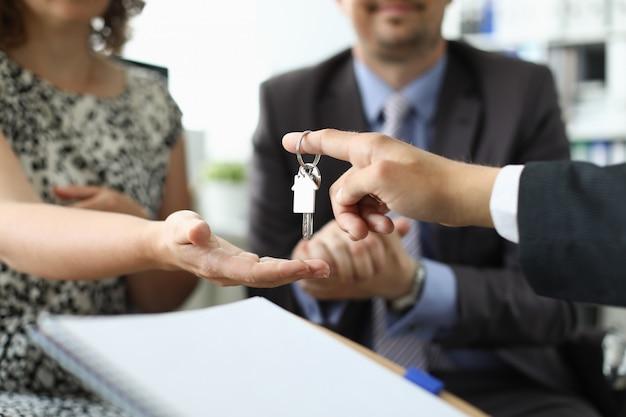 Mão do corretor de imóveis segura casa chave contra escritório Foto Premium
