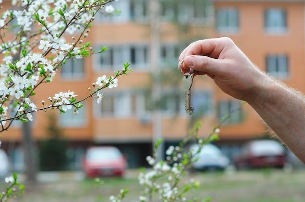 Mão do corretor segurando a chave para uma casa de sonho Foto Premium