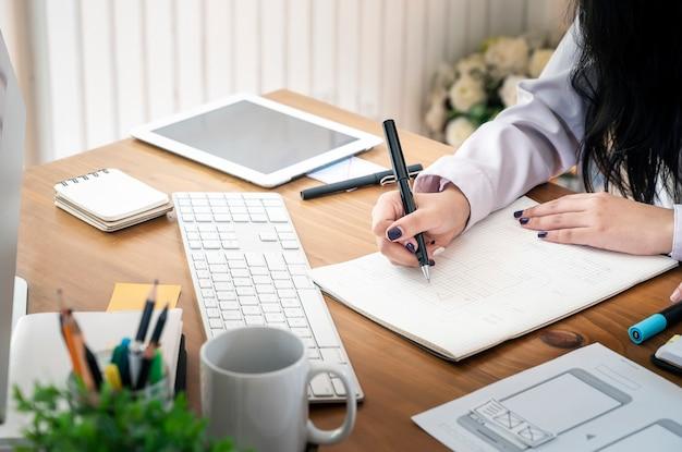 Mão do desenhista fêmea que trabalha com seu projeto novo no escritório. Foto Premium