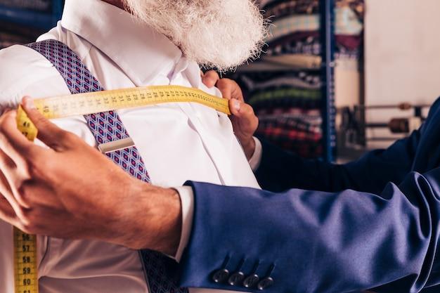 Mão do designer de moda, medição do peito do seu cliente com fita métrica amarela Foto gratuita