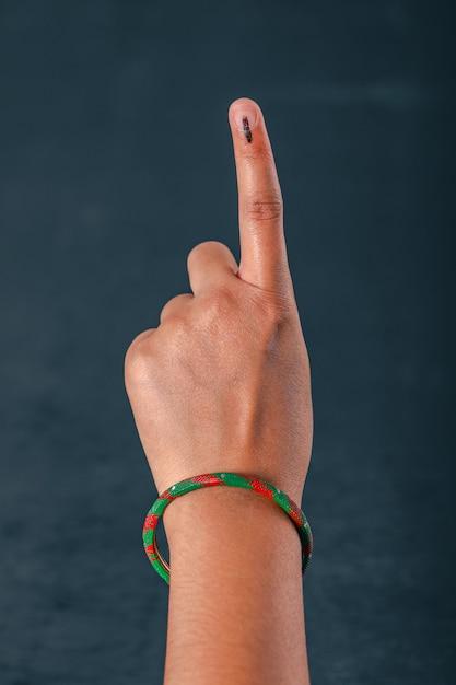 Mão do eleitor indiano com sinal de voto após voto de seleção nas eleições Foto Premium