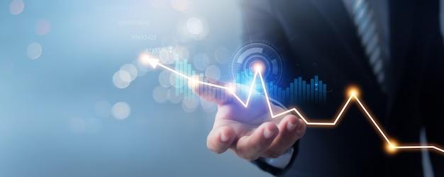 Mão do empresário de terno segura gráfico de finanças de negócios bancários em desfoque suave de fundo azul Foto Premium