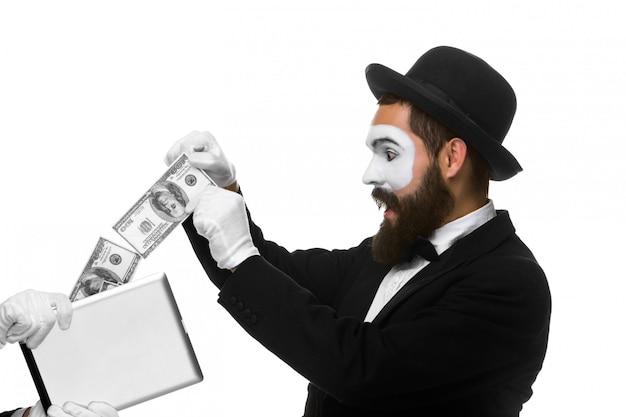 Mão do empresário em forma de mímica extrair dinheiro do tablet pc Foto gratuita