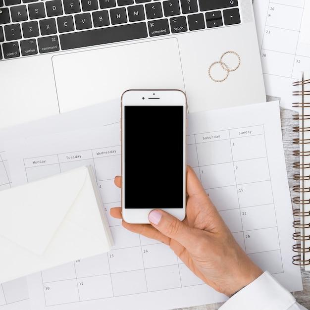 Mão do empresário segurando smartphone sobre o calendário com envelope; laptop e alianças de casamento Foto gratuita