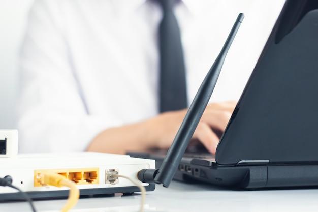 Mão do engenheiro de rede digitando no teclado do laptop ao lado Foto Premium