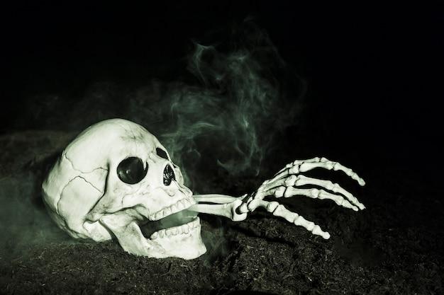 Mão do esqueleto saindo do crânio no chão Foto gratuita