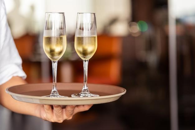 Mão do garçom traz copos com champanhe em uma bandeja. Foto Premium