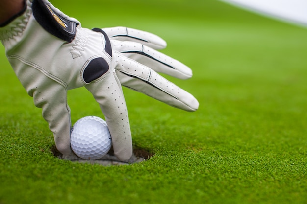 Mão do homem, colocando uma bola de golfe no buraco no campo verde Foto Premium