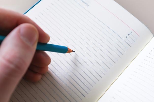 Mão do homem com escrita do lápis no caderno branco. conceito para educação e negócios Foto Premium