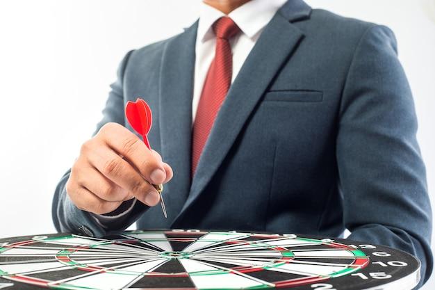 Mão do homem de negócio que guarda um alvo com os dardos que batem o centro sobre o fundo branco. Foto Premium