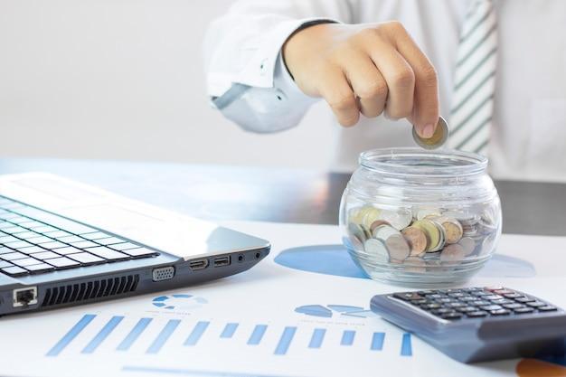 Mão do homem de negócios empilhados dinheiro moedas no pote, conceito como finanças, poupança e capital bancário Foto Premium