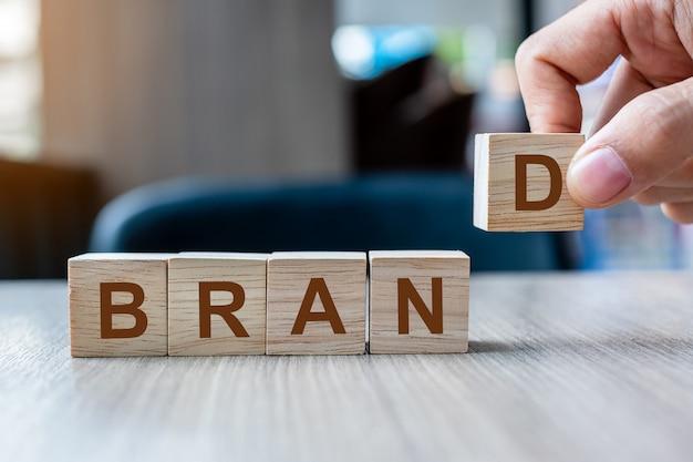 Mão do homem de negócios que guarda o bloco de madeira do cubo com palavra do negócio do marca no fundo da tabela. Foto Premium