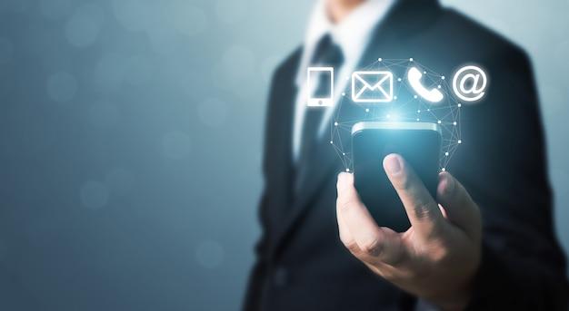 Mão do homem de negócios que guarda o telefone esperto com telefone celular, correio, telefone e endereço do ícone. centro de atendimento ao cliente entre em contato conosco conceito Foto Premium