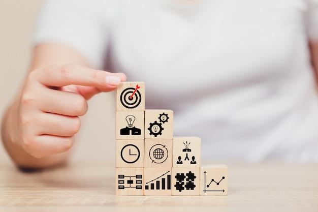 Mão do homem de negócios que põe o bloco de madeira do cubo na parte superior com conceito do sucesso do alvo. Foto Premium