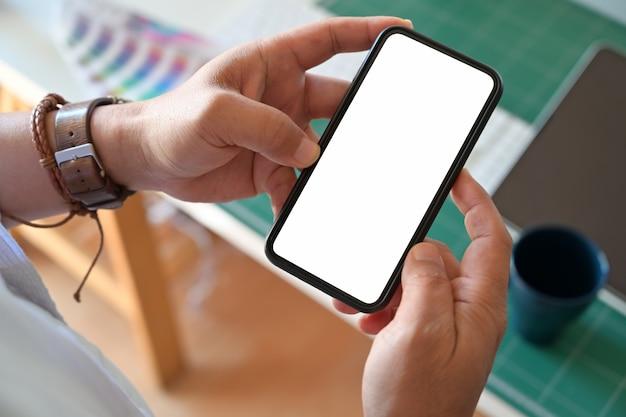 Mão do homem que guarda o telefone esperto móvel da tela vazia no local de trabalho. Foto Premium