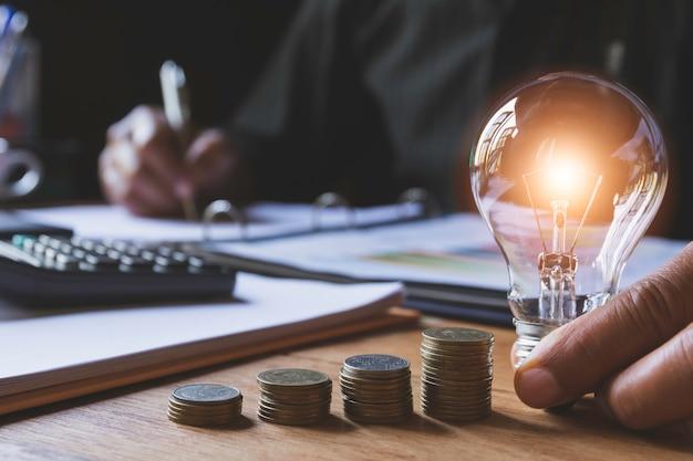 Mão do homem que guarda uma ampola com a pilha de moedas para explicar e conceito criativo. Foto Premium