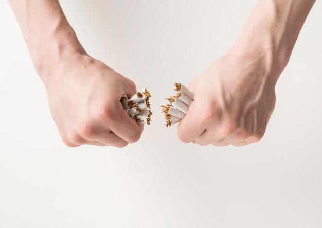 Mão do homem, quebrando o monte de cigarros sobre o pano de fundo branco Foto gratuita