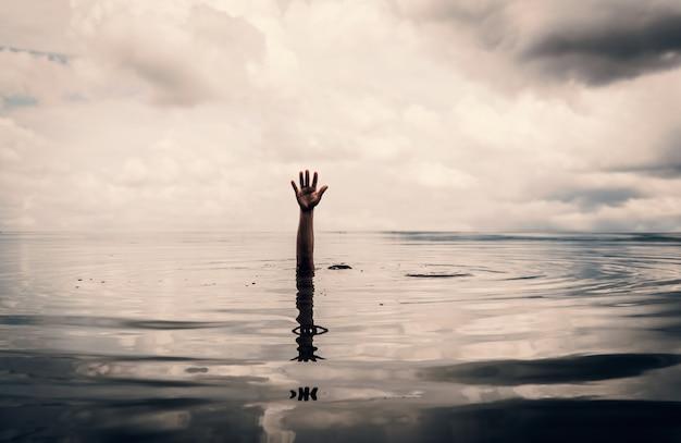 Mão do homem quer ajudar depois de se afogar no lago Foto Premium