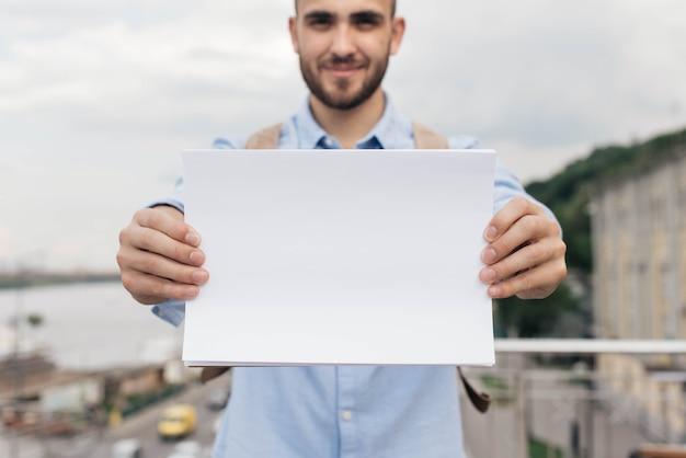 Mão do homem, segurando o papel branco em branco Foto gratuita