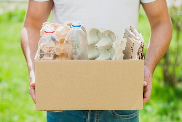 Mão do homem segurando produtos de reciclagem na caixa de papelão Foto gratuita
