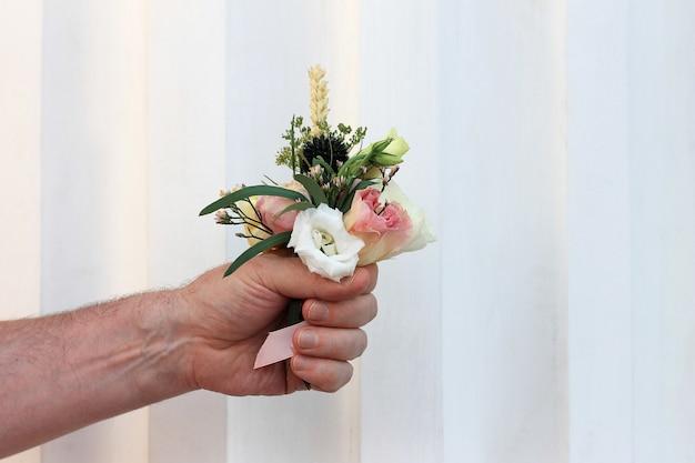 Mão do homem segurando um pequeno buquê lindo de flores Foto Premium