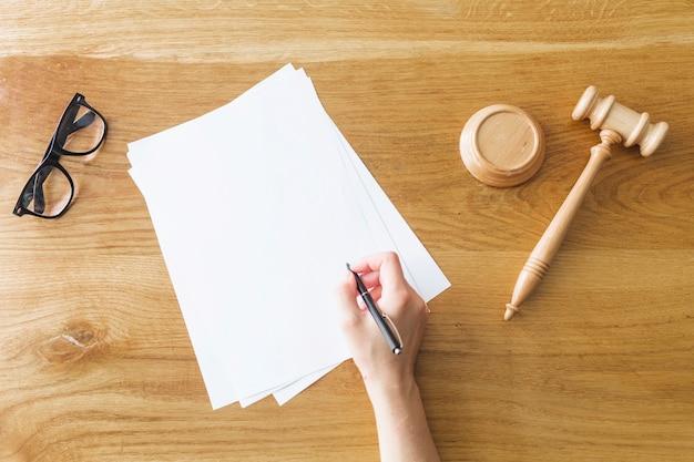 eb869ebc5164b Mão do juiz, escrevendo no papel perto de martelo e óculos na mesa ...