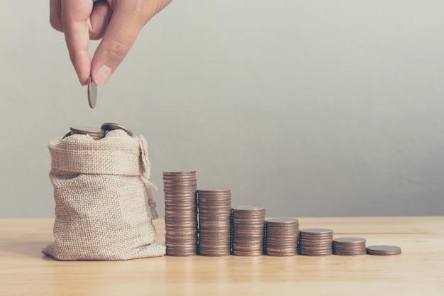 Mão do macho ou da fêmea que põe moedas no saco do dinheiro com etapa da pilha da moeda crescimento crescente que conserva o dinheiro, investimento do negócio da finança do conceito Foto Premium