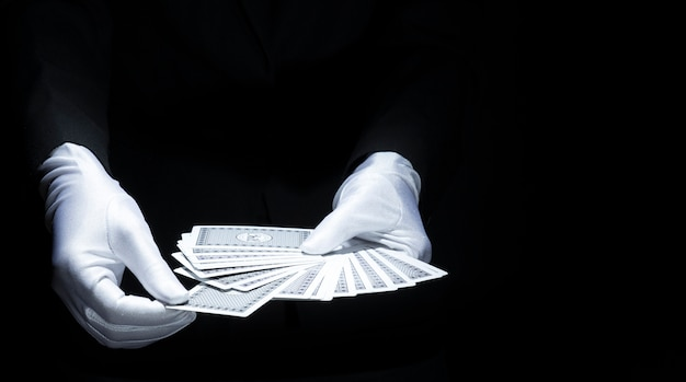 Mão do mago que seleciona o cartão do baralho ventilado de cartão de jogo contra o fundo preto Foto gratuita